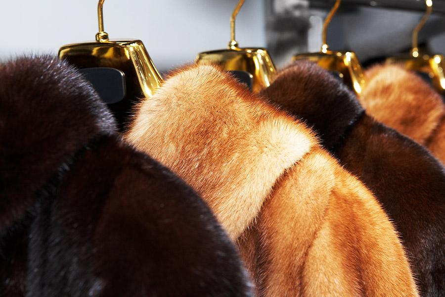 Furrier and Garment Dealer Insurance - Closeup of Vintage Fur Coats on a Sale Rack