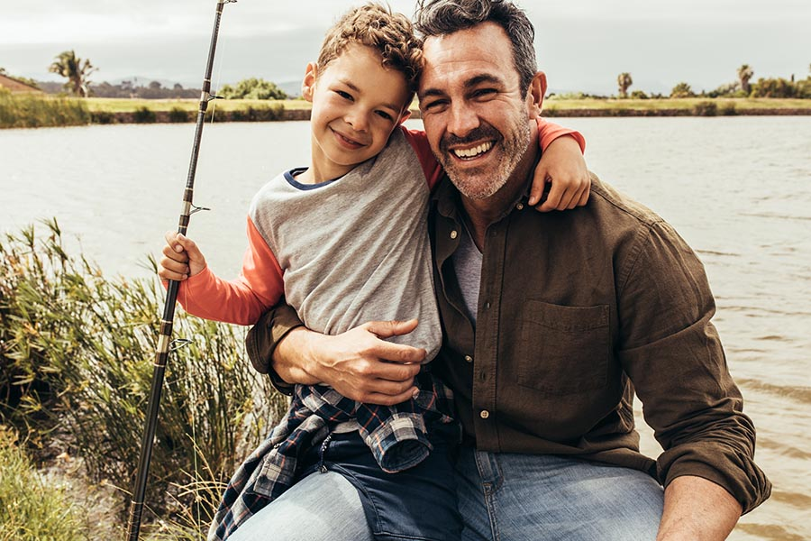 Personal Insurance - Father and Young Son Smiling and Holding Fishing Equipment Next to a Lake